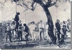 """Die foto wat een van Rhodes se huursoldate van die """"Hanging Tree"""" by Harare geneem het toe Lobengula se indoenas daar opgehang is. Die foto is in Kimberley in 'n kroeg of barbierswinkel ten toon gestel tot vermaak van die diamantdelwers. Toe Olive Schreiner dit sien, was sy hewig ontsteld, en toe sy verneem wat Rhodes en sy bende moordenaars alles in Masjonaland en Matabeleland aanvang, het sy die allegoriese verhaal, Trooper Peter Halket of Mashonaland, geskryf en alles onthul. Die foto het sy voorin die boek laat plaas. Dit is in 1897 in Londen gepubliseer."""