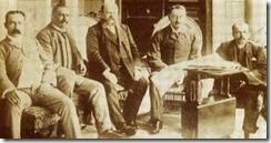 Cecil John Rhodes, naasregs, Leander Starr Jameson, heel regs, en ander samesweerders op die stoep van Groote Schuur in Kaapstad besig om die besonderhede van die inval in die Transvaalse Boererepubliek te bespreek. Hulle wou die ZAR bekom om eienaarskap van die ryk goudrif van die Witwatersrand te bekom. In Londen het die Britse regering van Joseph Chamberlain die staatsgreep gesteun. Van links sit K. Kineaid-Smith, Alfred Beit, Frank Rhodes, Cecil John Rhodes en Leander Starr Jameson.