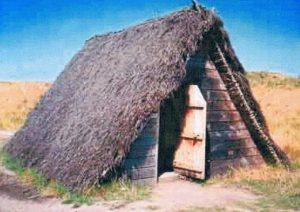Figuur 2.  'n Britse rekonstruksie van 'n wigvormige dakhuis wat in die grond ingegrawe is. Uit: https://www.bedesworld.co.uk/site_2003-05-10/building/n… 2008-02-3.